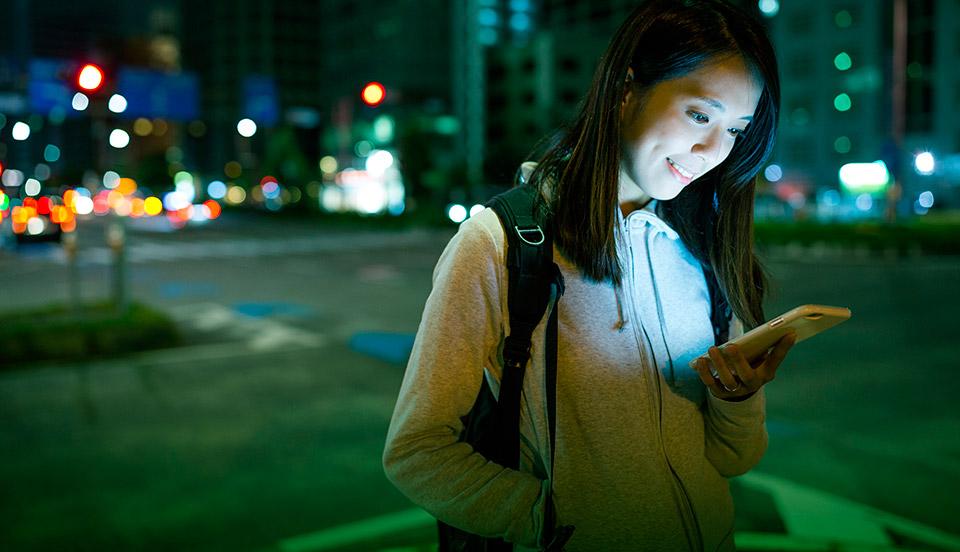 Bild av flicka som tittar på sin telefon